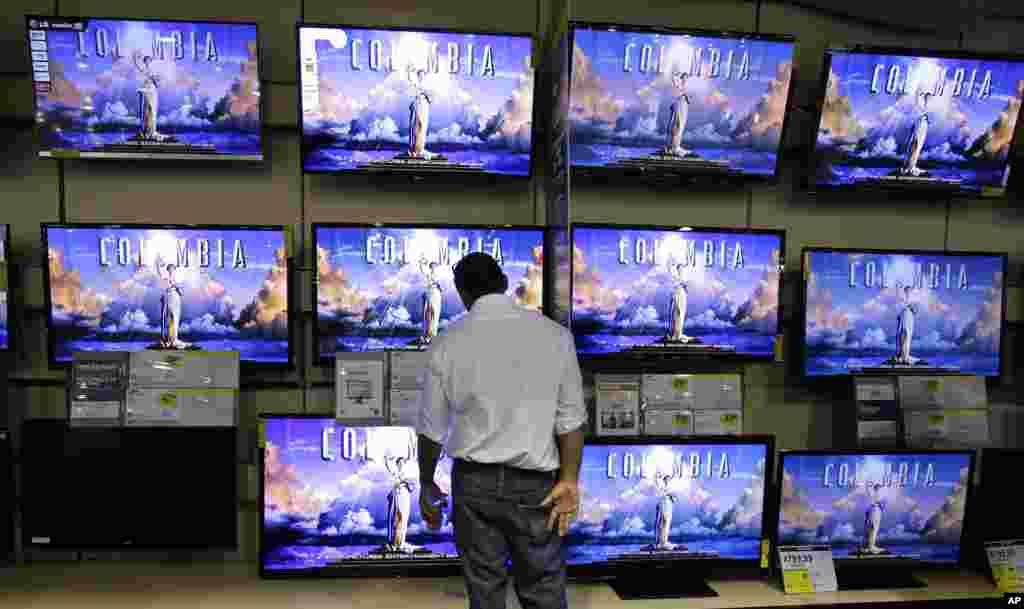 Un comprador observa la sección de televisores para ver qué modelo le conviene en la tienda Best Buy en Tenesí.
