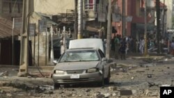 A body is seen at the site of a bomb explosion at a road in Kaduna, Nigeria, April 8, 2012.