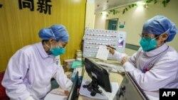 中国武汉一所医院的医务人员戴着口罩在工作。(2020年1月30日)
