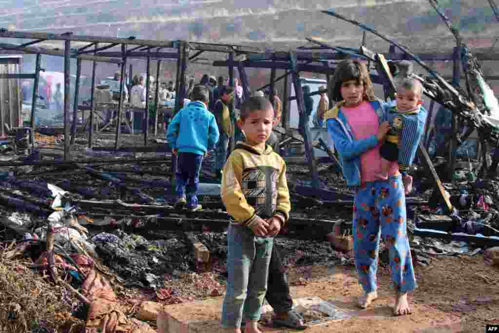 Syrian refugees check the damage following a fire that ripped through their refugee camp in the village of Yammouneh in Lebanon's eastern Bekaa Valley.