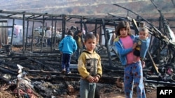 FILE - Syrian refugees check the damage following a fire that ripped through their refugee camp in the village of Yammouneh in Lebanon's eastern Bekaa Valley on Dec. 3, 2018.