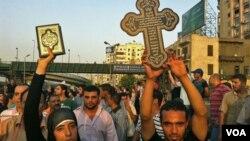Perempuan muslim membawa al-Quran (kiri) untuk menunjukkan solidaritas dalam unjuk rasa warga Kristen Koptik di ibukota Kairo (10/10).