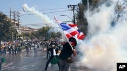 12月1日在曼谷,反政府示威者把警方发射的催泪瓦斯瓶扔回去