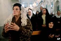 FILE - Syrian Christians and Muslims offer prayers for nuns held by rebels, at the Greek Orthodox Mariamiya Church in Damascus, Syria, Dec. 8, 2013.