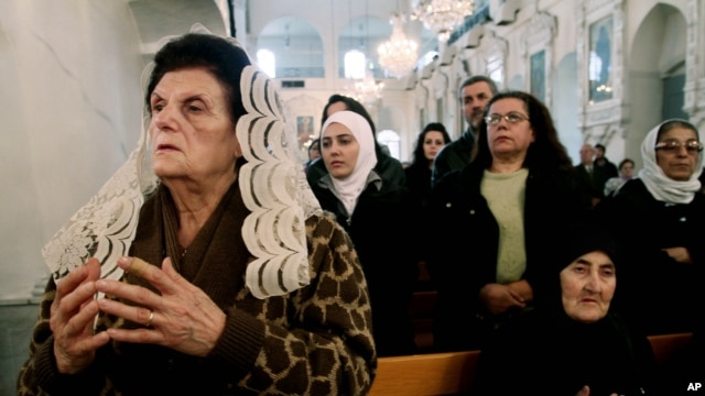 Syrian Christians and Muslims offer prayers for nuns held by rebels, at the Greek Orthodox Mariamiya Church in Damascus, Syria, Sunday, Dec. 8, 2013.
