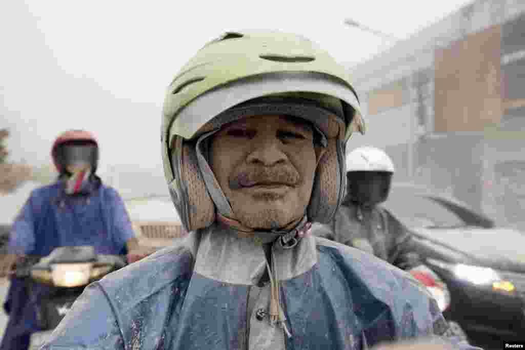 Seorang pengendara motor di Yogyakarta berselimut abu dari Gunung Kelud di Kediri, Jawa Timur, yang meletus Kamis malam (13/2). (Reuters/Dwi Oblo)