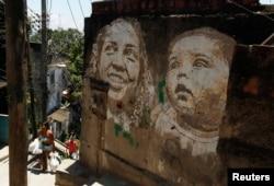 People walk past graffiti in the Morro da Providencia slum in Rio de Janeiro, Nov. 29, 2012. The artwork of Portuguese artist Alexandre Farto, a k a Vhils, decorates some walls with faces that represent the people who live in Providencia.