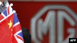 Radnik u fabrici automobila u Birmingemu drži zastave Kine i Velike Britanije, tokom posete kineskog premijera