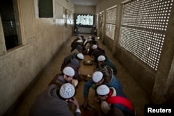 In this Feb. 1, 2015 photo, Pakistani students of a madrassa, or Islamic school, eat their lunch at their seminary in Islamabad, Pakistan.