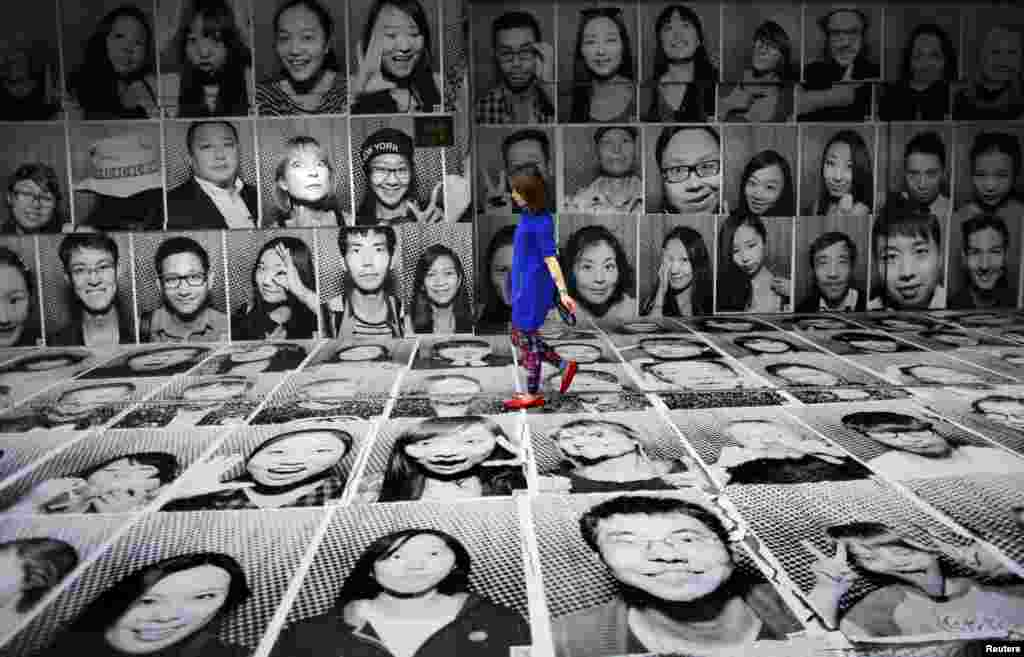 A woman walks through a display of portraits which were made as part of the Inside Out art project by French artist JR at Xintiandi area, in downtown Shanghai, China.