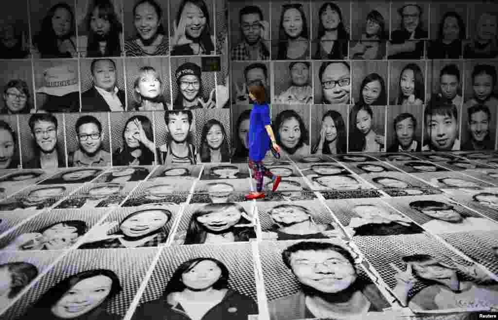 중국 상해 시내에서 프랑스 예술가 JR의 작품 전시회 '인사이드 아웃'이 열린 가운데, 한 여성이 초상화를 모아 만든 작품 위를 걸어가고 있다.