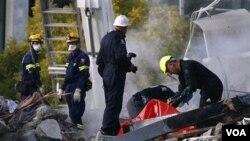 Tim penyelamat mengangkat seorang korban tewas dari reruntuhan bangunan di kota Christchurch (24/2).