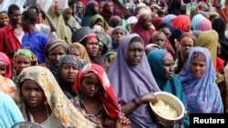 Internally displaced Somali women wait for food at a camp in the capital Mogadishu, July 2011.