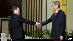 Wang Yu-chi, left, head of Taiwan's Mainland Affairs Council, shakes hands with Zhang Zhijun, director of China's Taiwan Affairs Office, Nanjing, Feb. 11, 2014.