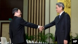 Wang Yu-chi, front left, head of Taiwan's Mainland Affairs Council, shakes hands with Zhang Zhijun, front right, director of China's Taiwan Affairs Office, before their meeting in Nanjing, in eastern China's Jiangsu Province, Feb. 11, 2014.