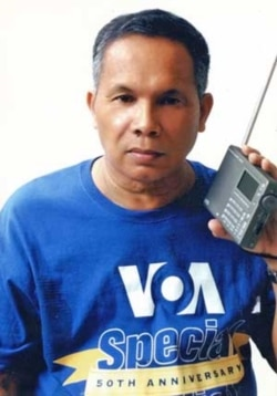 Luis L.L. Sevilla of the Philippines, a VOA listener since 1967 and a winner of the Special English 50th anniversary T-shirt, listening to his Eton E5 receiver.