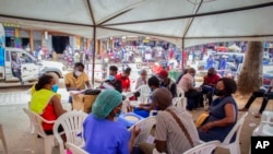 FILE - People wait to receive coronavirus vaccinations at a streetside vaccination tent in Kampala, Uganda, Sept. 7, 2021. Uganda is accelerating its vaccination drive and is now reaching out to people at bars and entertainment venues.