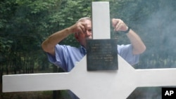 FILE - An Australian veteran adjusts the plague of the cross during a ceremony to mark 40th anniversary of the battle of Long Tan in southern Ba Ria Vung Tau province, Vietnam, Aug. 18, 2006.