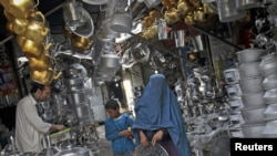 An Afghan woman carries a steel tray in a market at the old part of Kabul, May 9, 2012.