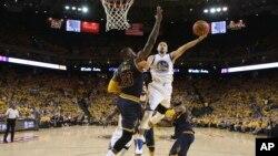 Stephen Curry (30) Golden State Warriors attaque avec le ballon face à LeBron James (23) de Cleveland Cavaliers au cours de la première mi-temps du deuxième match de la finale NBA de basket-ball à Oakland, en Californie., 5 juin 2016. (Ezra Shaw, Getty Images via AP, Pool
