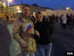 莫斯科红场支持克里米亚并入俄罗斯的集会结束后,普京的两名支持者亚历山大和安娜 (美国之音 白桦拍摄)