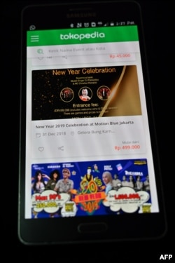 This picture taken in Jakarta on Dec. 12, 2018 shows a website of Tokopedia on a mobile phone selling tickets.