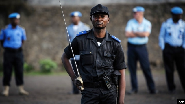 United Nations peacekeepers stand in the background as a Congolese national police officer holds a sword and stands with other officers during a gathering in Goma, in the Democratic Republic of Congo, December 2, 2012.