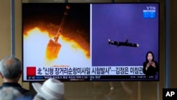 People watch a TV screen showing a news program reporting about North Korea's long-range cruise missiles tests with images in Seoul, South Korea, Monday, Sept. 13, 2021. (AP Photo/Lee Jin-man)