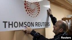 یک مرد در حال نصب تابلوی شرکت تامسون رویترز در یکی از دفاتر بین المللی این خبرگزاری.