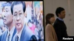 Orang-orang berlalu melewati TV yang menayangkan laporan mengenai Jang Song Thaek, paman dari penguasa Korea Utara Kim Jong Un di sebuah stasiun kereta di Seoul 3/12/2013.