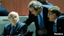 ປະທານ ສະມາຄົມເຕະບານຢູໂຣບ ຫຼື UEFA ທ່ານ Michel Platini (ກາງ) ໂອ້ລົມກັບ ປະທານອົງການຄຸ້ມຄອງເຕະບານໂລກ ຫຼື FIFA ທ່ານ Sepp Blatter (ຊ້າຍ) ແລະ ທ່ານ Jerome Valcke, ເລຂາທິການໃຫຍ່ ຂອງ ອົງການ FIFA, ຢູ່ທີ່ ກອງປະຊຸມປະຈຳປີ ຂອງອົງການ FIFA ຄັ້ງທີ 65 ໃນນະຄອນ Zurich, Switzerland, ວັນທີ 29 ພຶດສະພາ 2015.