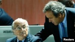 Michel Platini, président de l'UEFA, débout, discute avec Sepp Blatter, assis, à gauche, lors du 65e Congrès de la Fifa à Zurich, Suisse, le 29 mai 2015.