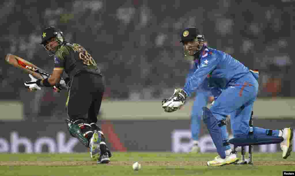 بھارتی کپتان اور وکٹ کیپر دھونی پاکستانی بلے باز عمر اکمل کی جانب سے لگائے گئے اسٹروک پر گیند کو جاتا دیکھ رہے ہیں