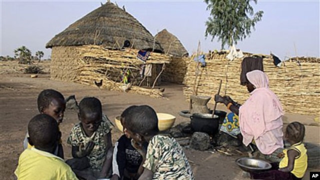 A Nigerian woman cooks millet paste as children eat breakfast from a shared bowl in the village of Tamou, 60 kilometers outside Niamey, Niger, Feb 2010 (file photo)
