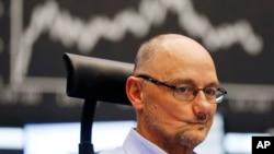 A trader grimaces as he watches his screens at the stock market in Frankfurt, Germany, July 6, 2015.