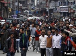People stand on a road after vacating buildings following an earthquake in Srinagar, October 26, 2015.