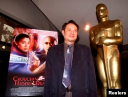 "FILE - Director Ang Lee stands next to the movie poster for his Academy Award-nominated fi   lm, ""Crouching Tiger, Hidden Dragon,"" at the Academy of Motion Pictures of Arts and Sciences in Beverly Hills, March 23, 2001."