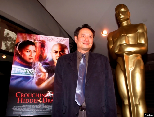 """Director Ang Lee stands next to the movie poster for his Academy Award-nominated film, """"Crouching Tiger, Hidden Dragon,"""" at the Academy of Motion Pictures of Arts and Sciences in Beverly Hills, March 23, 2001 
