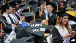 "A graduating student wears a cap reading ""hire me,"" as the City College of New York (CCNY) class of 2016 assemble for graduation, Friday June 3, 2016, in New York. First lady Michelle Obama delivered the keynote speech. (AP Photo/Bebeto Matthews)"