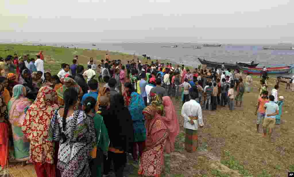 Bangladeshis watch a rescue operation from the banks of the Meghna River, Feb. 8, 2013.