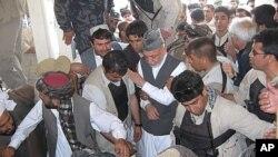 ປະທານາທິບໍດີອັຟການິສຖານ ທ່ານ Hamid Karzai (ກາງ) ໄປຮ່ວມພິທີສົ່ງສະການ ຂອງທ່ານ Ahmad Wali Karzai ນ້ອງຊາຍຕ່າງບິດາຂອງທ່ານ ໃນເຂດເມືອງ Dand ແຂວງການດາຮາໃນພາກໃຕ້ອັຟການິສ ຖານ (13 ກໍລະກົດ 2011)