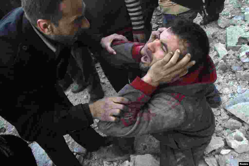 A man reacts after what activists said was an air raid by forces loyal to Syrian President Bashar Al-Assad in Aleppo's al-Marja district. More than 300 people have been killed in a week of air raids on the northern city of Aleppo and nearby towns, a monitoring group said.