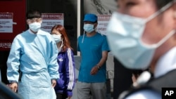 Hospital workers and visitors wearing masks to protect against the MERS, Middle East Respiratory Syndrome, virus at a quarantine tent in Seoul, South Korea June 3, 2015. (AP Photo/Ahn Young-joon)