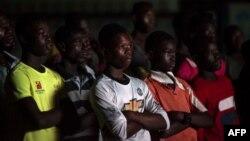 """Ces personnes regardent le documentaire """"Number 12"""" par le journaliste d'investigation Anas Aremeyaw Anas au sujet de l'ancien président de la Ghanian Football Association (GFA), Kwesi Nyantakyi, à Accra, le 10 juin 2018 (AFP PHOTO / CRISTINA ALDEHUELA)."""
