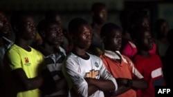 """Les gens regardent le documentaire """"Number 12"""" par le journaliste d'investigation Anas Aremeyaw Anas au sujet de l'ancien président de la Ghanian Football Association (GFA), Kwesi Nyantakyi, à Accra, le 10 juin 2018."""