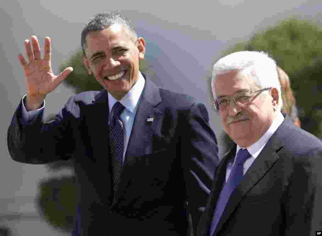 U.S. President Barack Obama waves to media as he walks with Palestinian President Mahmoud Abbas at the Muqata Presidential Compound in the West Bank town of Ramallah, March 21, 2013.