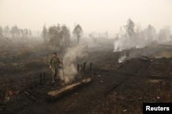 Seorang tentara memeriksa kebakaran lahan gambut dekat Palangkaraya, Kalimantan Tengah, 28 Oktober 2015. (Foto: Antara via Reuters)