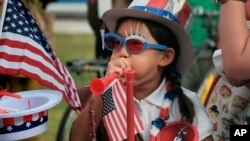 FILE - Eight year old Hana Cho from Girl Scout Troop 5665 tests out a horn prior to participating the 4th of July parade in Santa Monica, Calif. on Tuesday, July 4, 2017.