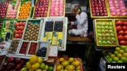 A fruit vendor speaks on his phone while sitting at his fruit stall at a wholesale market in Mumbai March 14, 2013. India's headline inflation picked up in February on higher fuel costs but another measure of price pressure cooled, reinforcing expectation