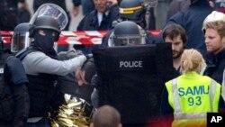 Comandos policiales llevan a un detenido en el operativo antiterrorista en Saint-Denis, cerca de París.